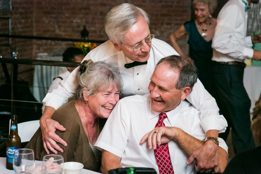Father of the bride hugging two guests at a DUMBO Loft wedding