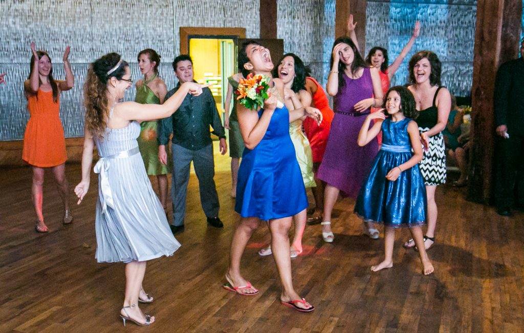 Female celebrating after catching bouquet at a DUMBO Loft wedding