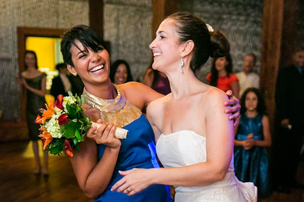 Woman holding bouquet and hugging bride at a DUMBO Loft wedding
