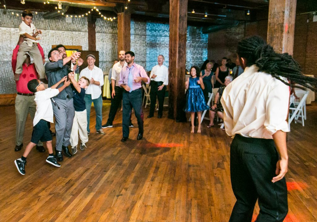 Male guests jumping to catch bow tie thrown by groom at a DUMBO Loft wedding
