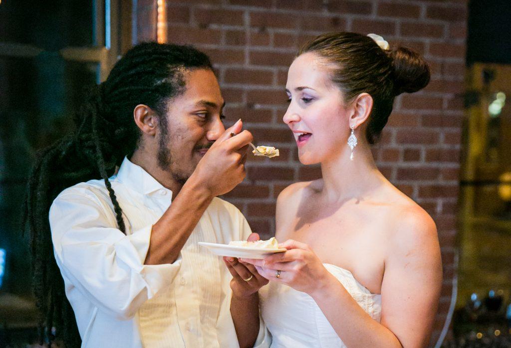 Groom feeding cake to bride at a DUMBO Loft wedding
