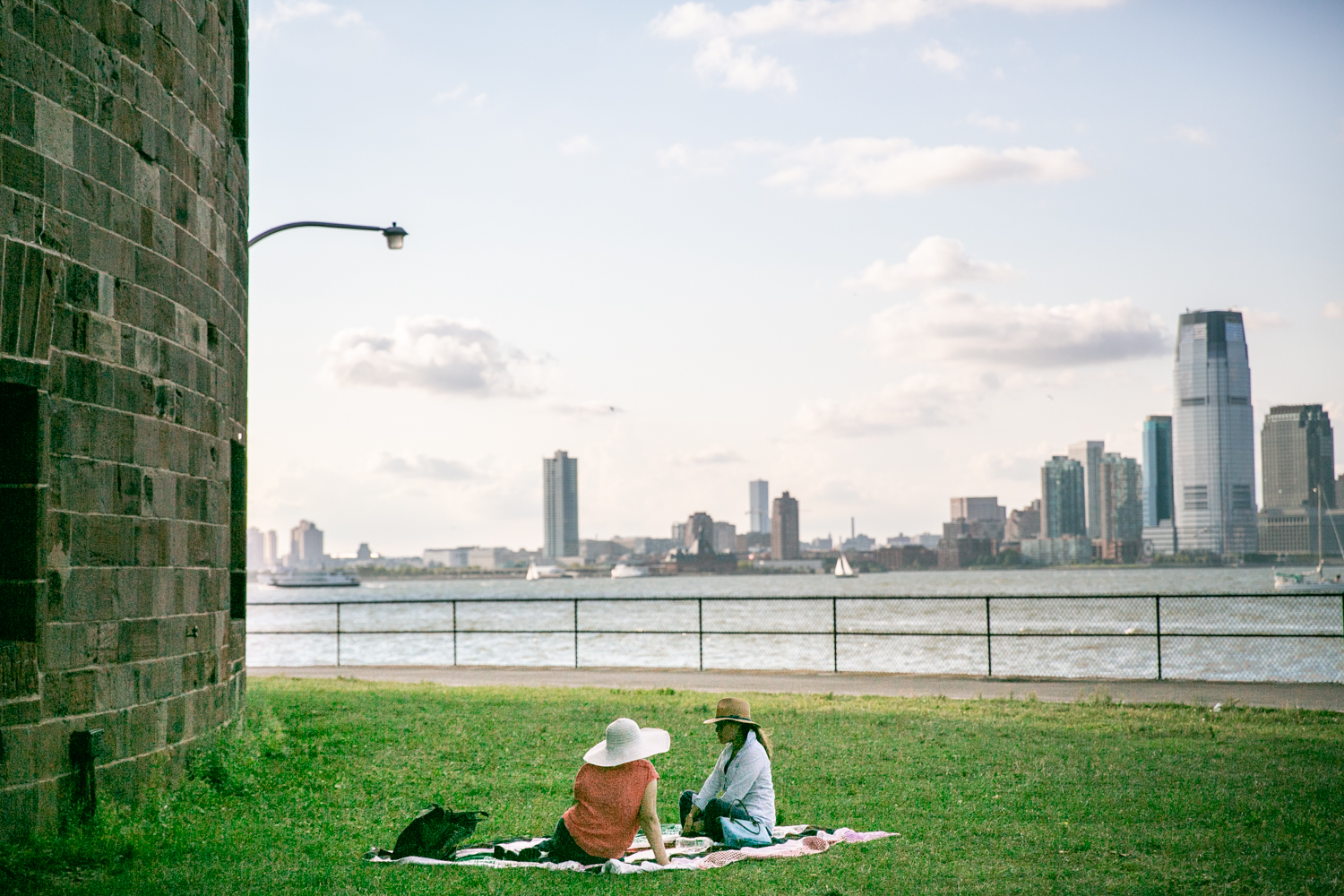 Governors Island photos of two women sitting in grass with NYC skyline in background