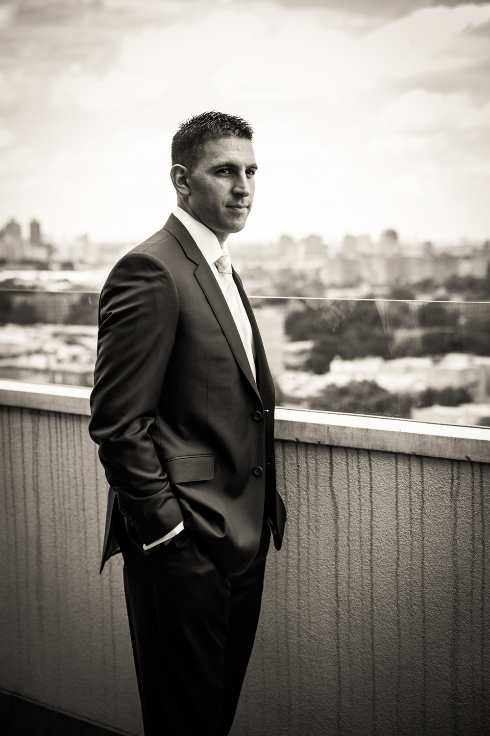 Black and white portrait of groom on rooftop