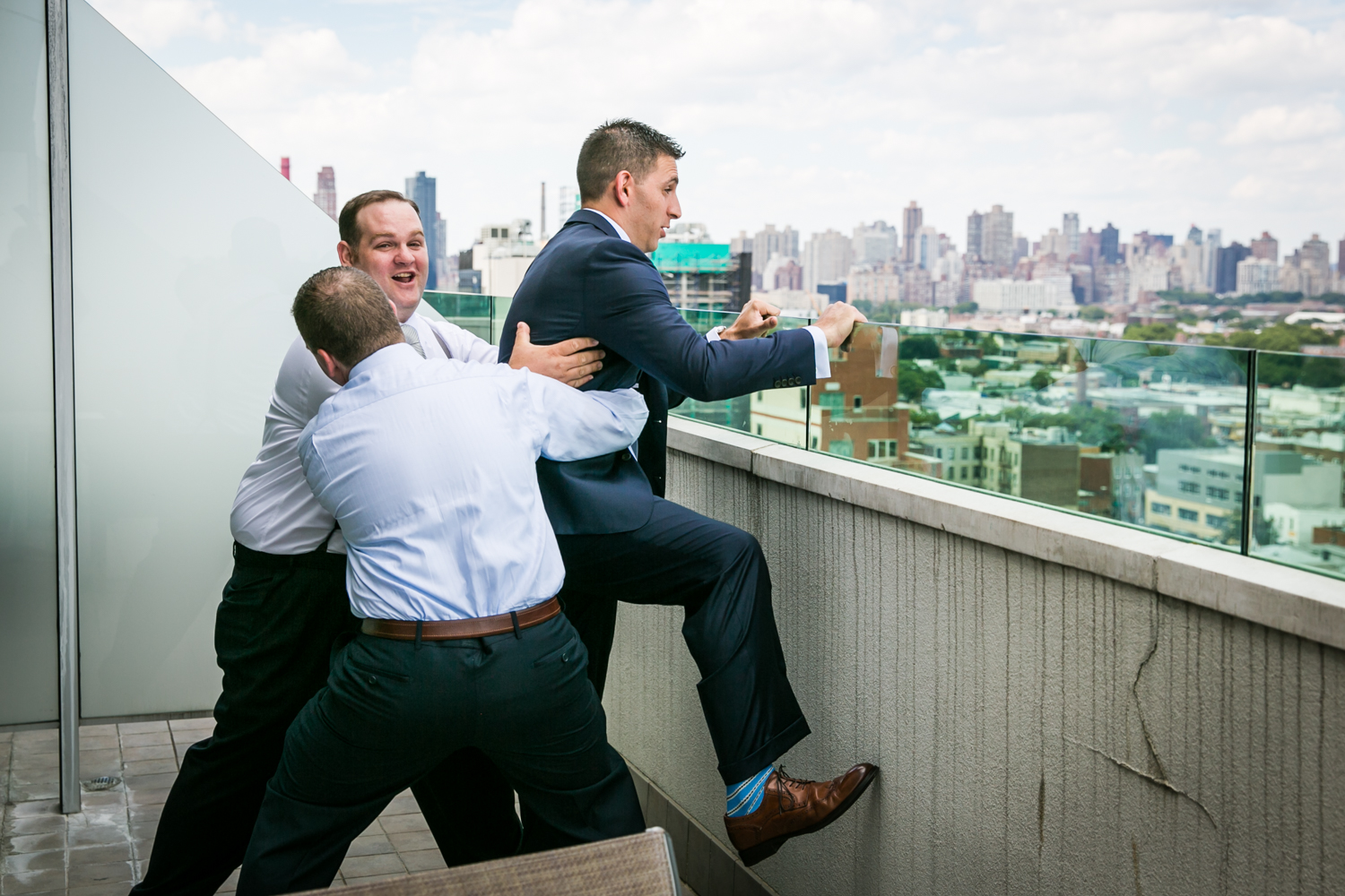 Groom attempting to leap from balcony and held back by two groomsmen