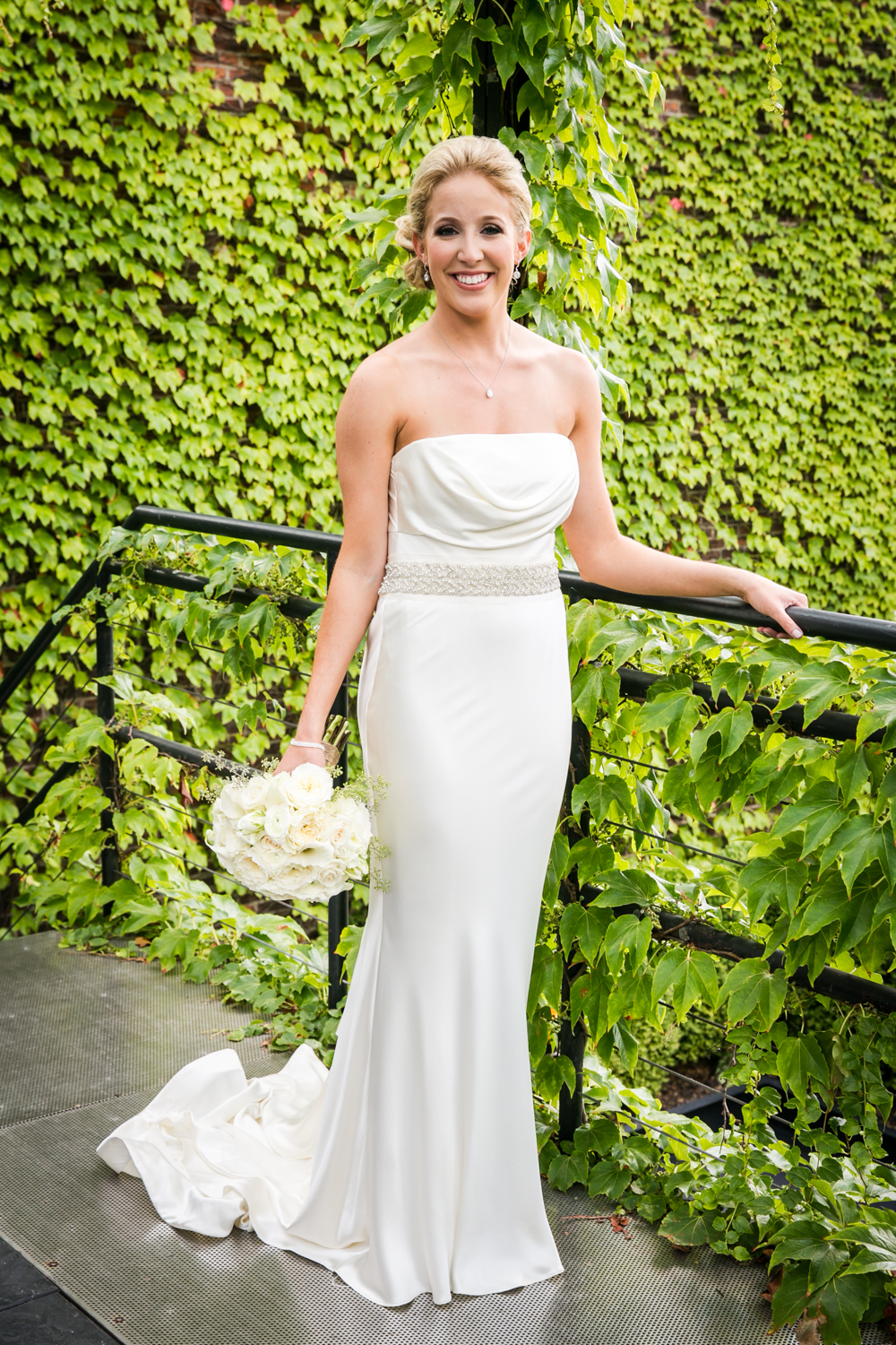 Portrait of bride wearing strapless gown and holding bouquet