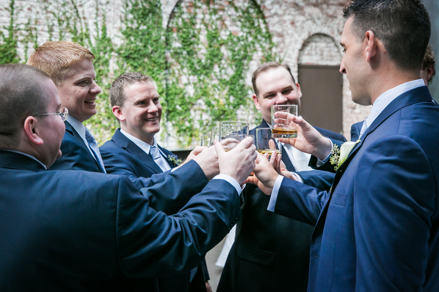 Groom and groomsmen cheering glasses for an article on how to become a wedding officiant in NYC