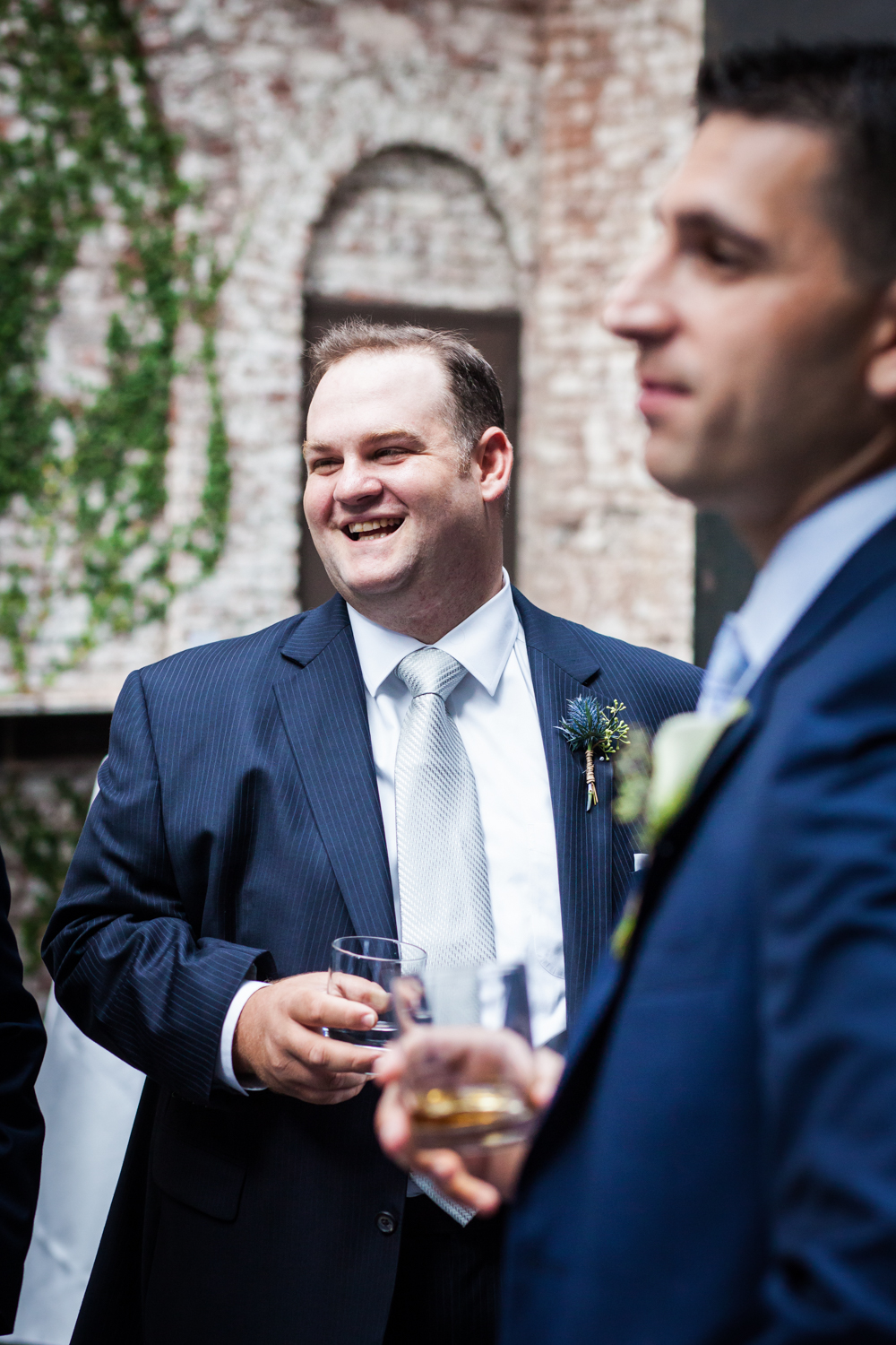 Groomsmen talking with other groomsmen and holding glass of scotch