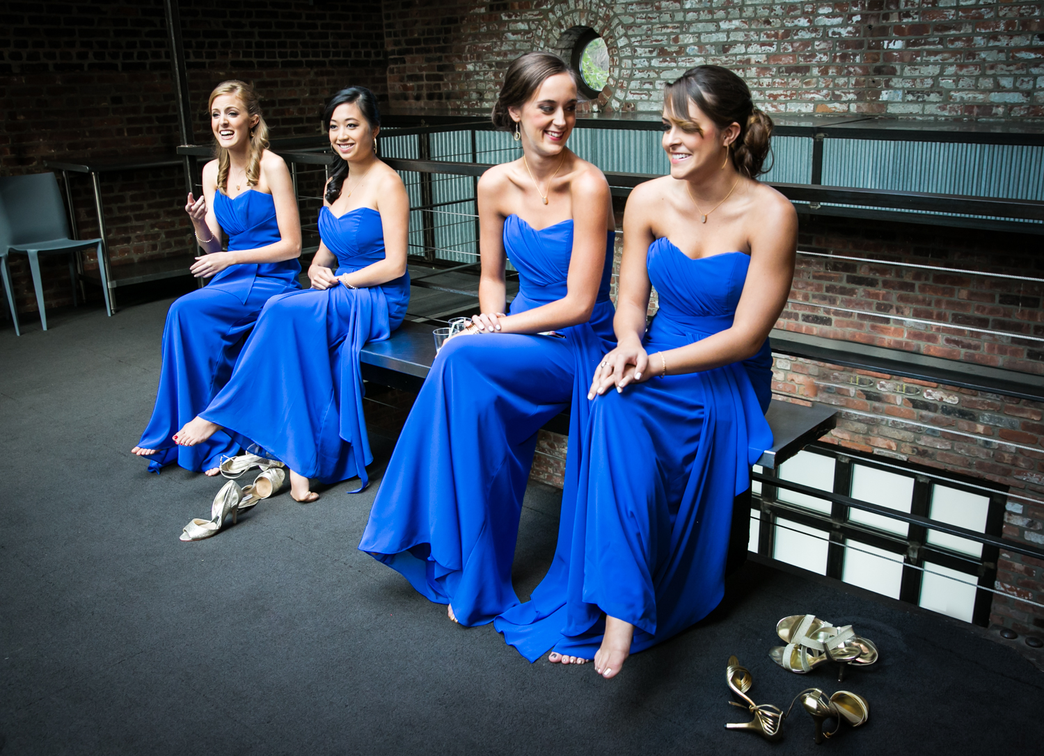 Bridesmaids wearing blue dresses and sitting on bench