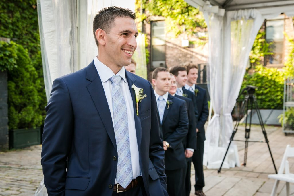 Groom waiting for bride to come down aisle for an article on how to become a wedding officiant in NYC