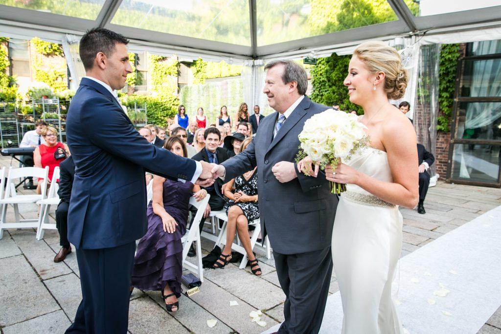 Groom shaking hand of bride's father during ceremony for an article on how to become a wedding officiant in NYC