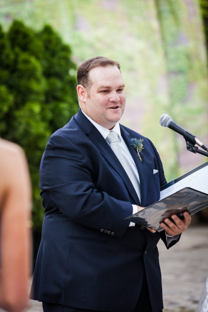 Man wearing suit and holding folder as wedding officiant for an article on how to become a wedding officiant in NYC