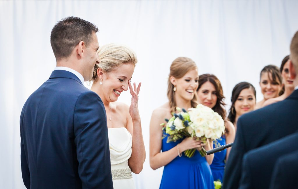 Bride wiping away tear during ceremony for an article on how to become a wedding officiant in NYC