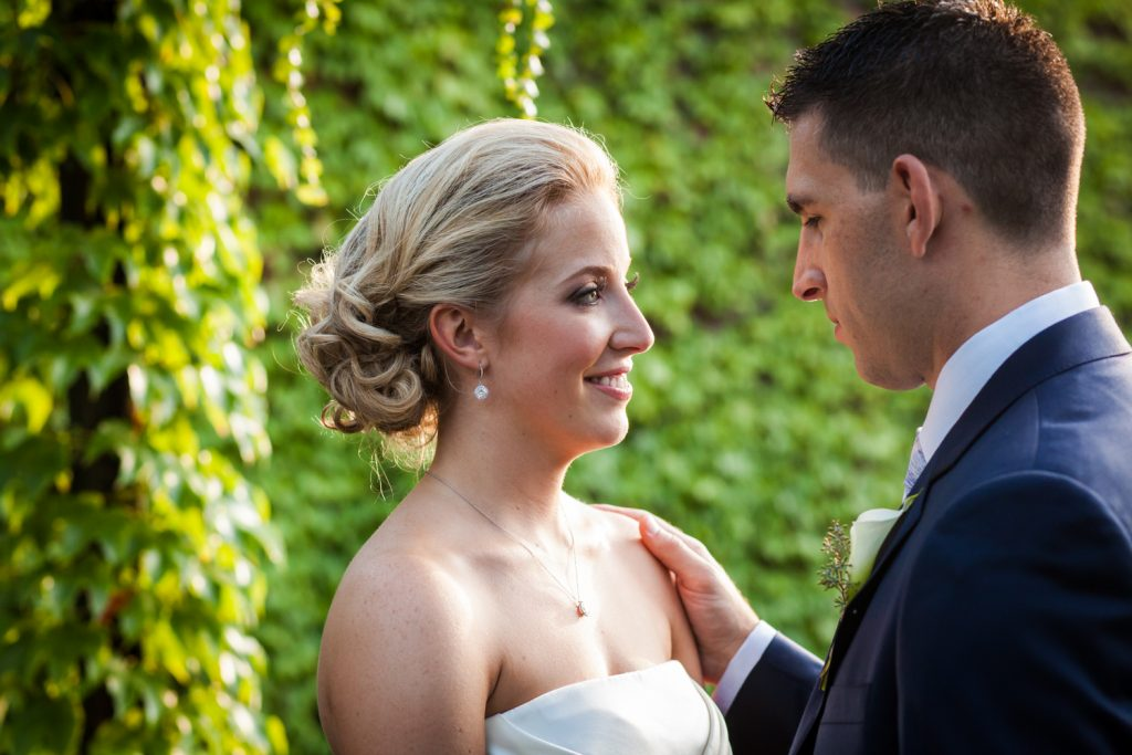 Bride and groom against ivy-covered wall for an article on how to become a wedding officiant in NYC