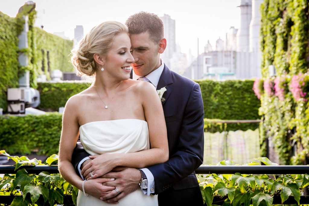 Bride and groom hugging against railing for an article on how to become a wedding officiant in NYC