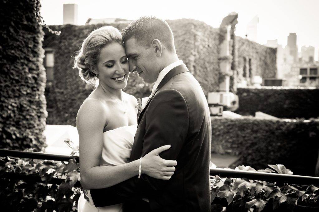 Black and white photo of groom hugging bride for an article on how to become a wedding officiant in NYC