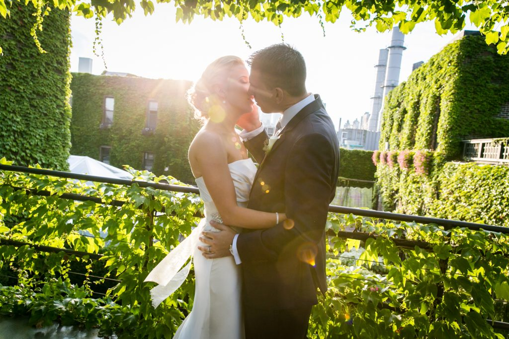 Bride and groom kissing with sun flair for an article on how to become a wedding officiant in NYC