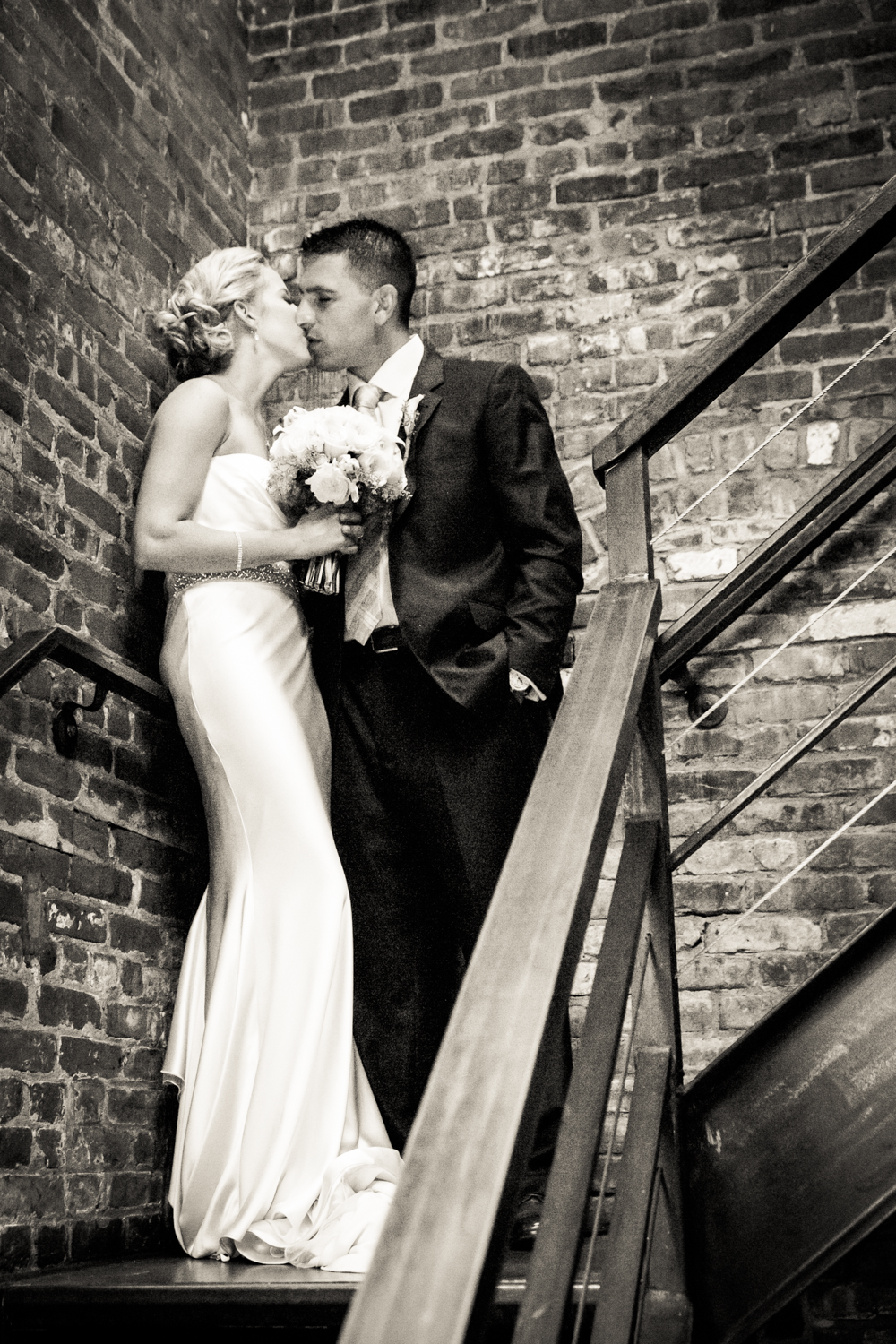 Black and white photo of bride and groom in brick stairwell