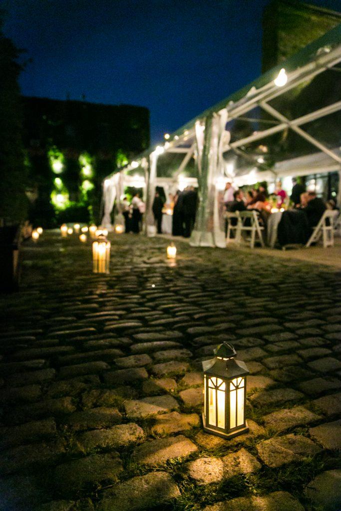 Lanterns lit at night on cobblestone street