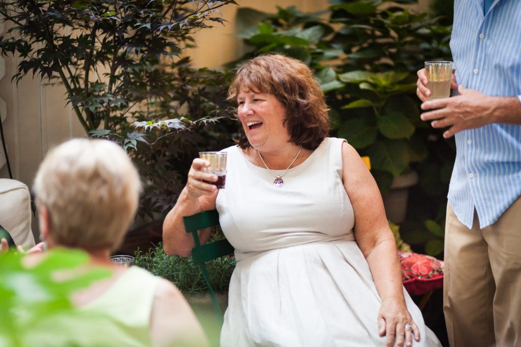Woman wearing white dress holding drink at a NYC rehearsal dinner
