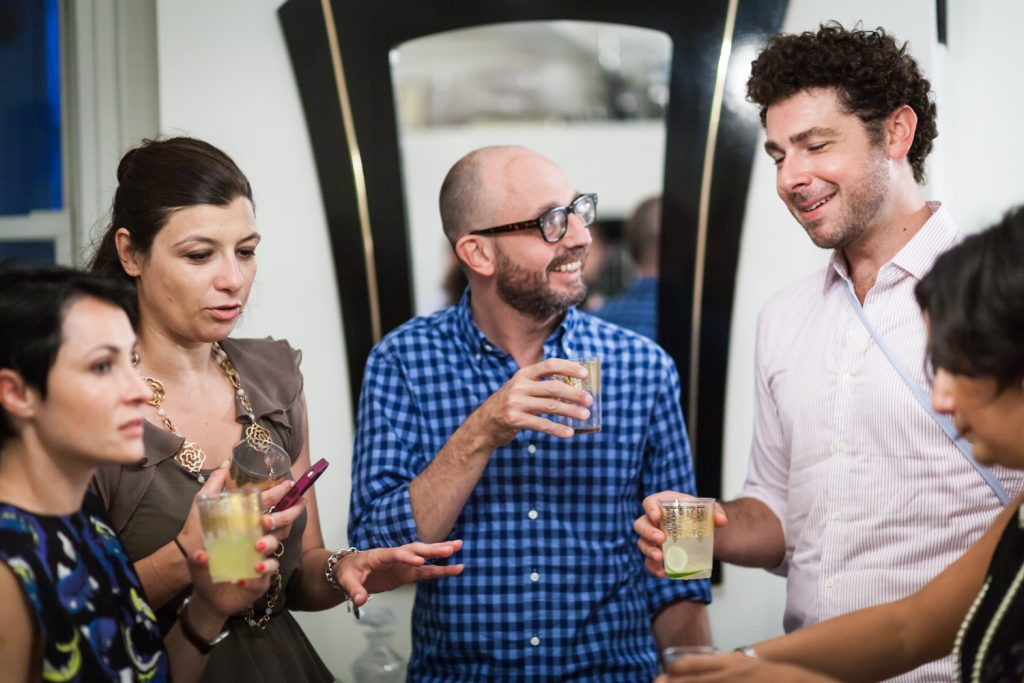 Five guests talking with drinks in hand at a NYC rehearsal dinner