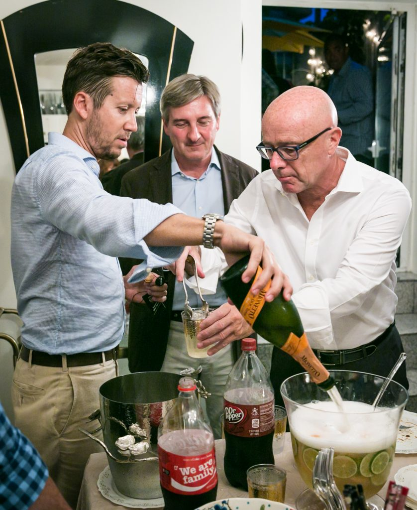 Man pouring champagne into a punch bowl with two guests