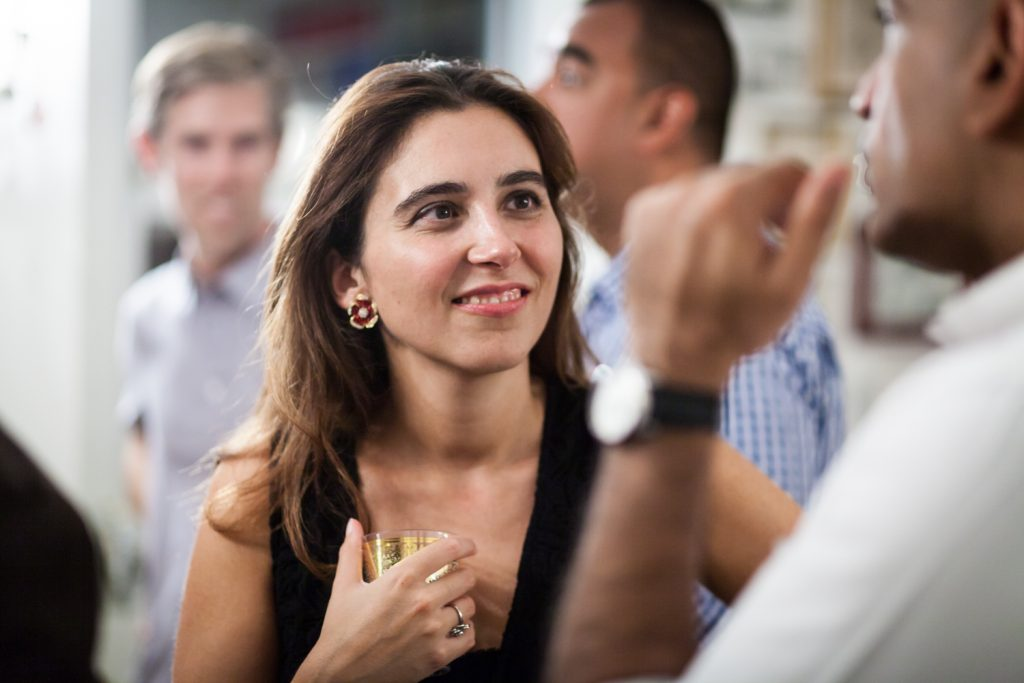 Woman holding drink and listening to guest at a NYC rehearsal dinner