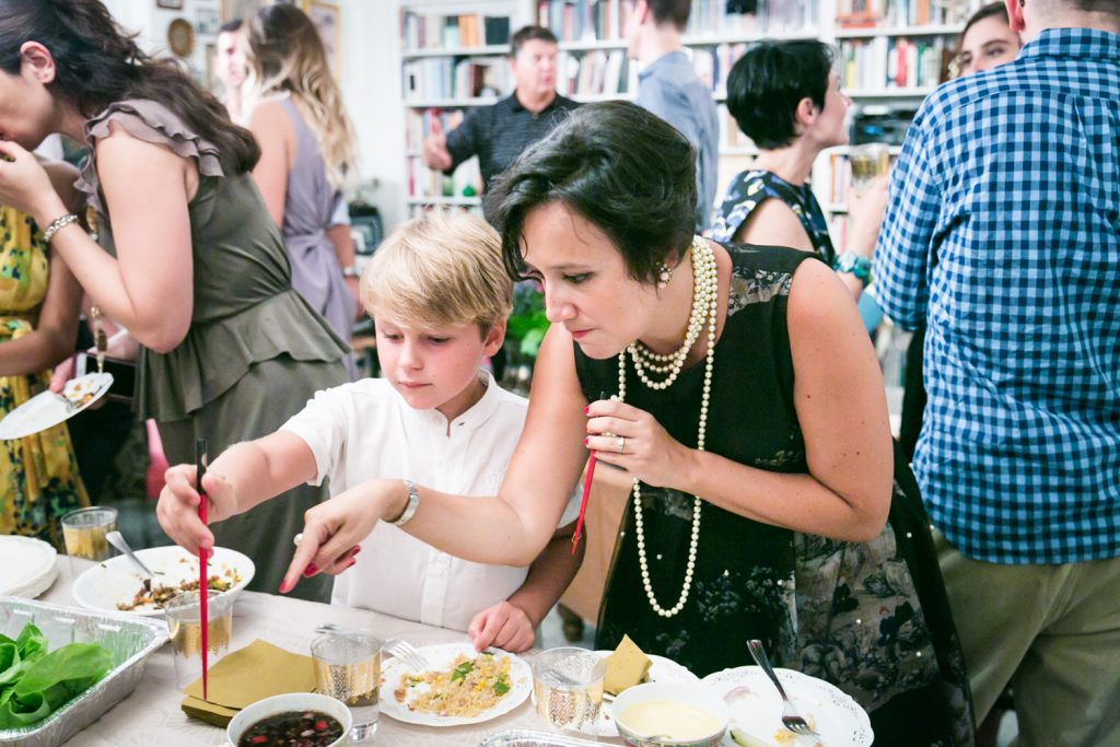 Woman pointing out food at a buffet to young boy