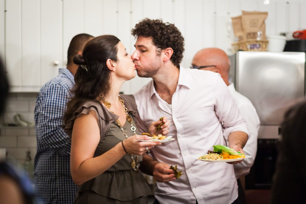 Couple holding plates and kissing