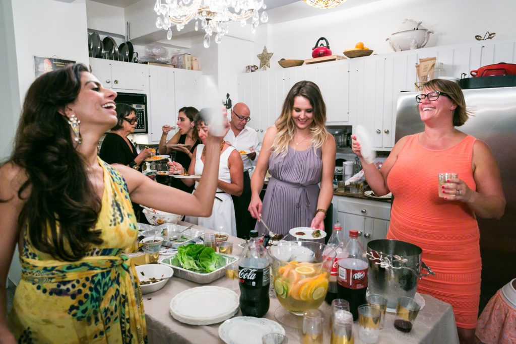 Guests enjoying a party in a Manhattan apartment kitchen