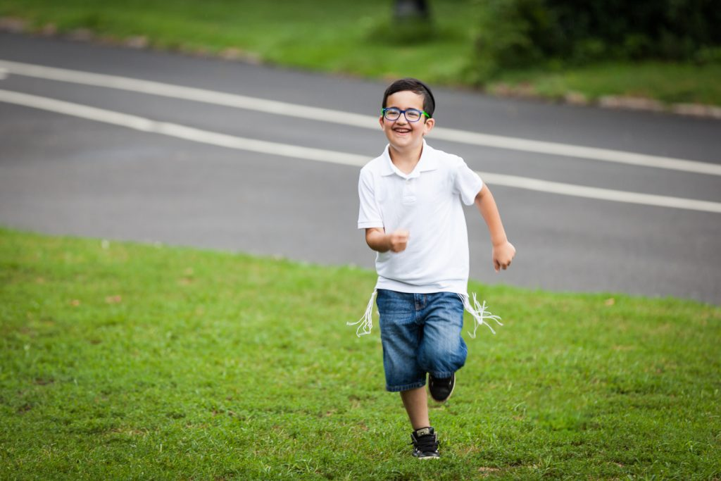 Prospect Park family photos of little boy wearing tzitzit and running