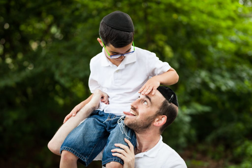 Man holding boy on his shoulder and making funny face