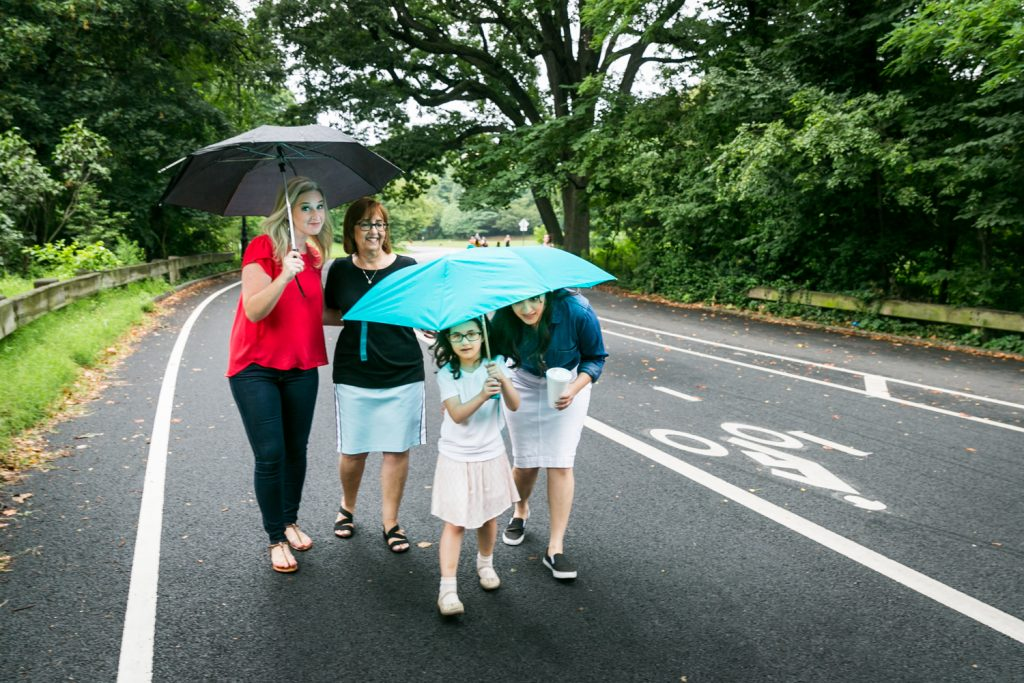 Three woman and little girl walking down road under umbrellas