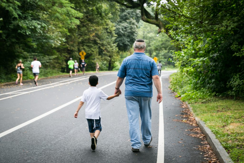 Grandfather holding grandson's hand and walking down road