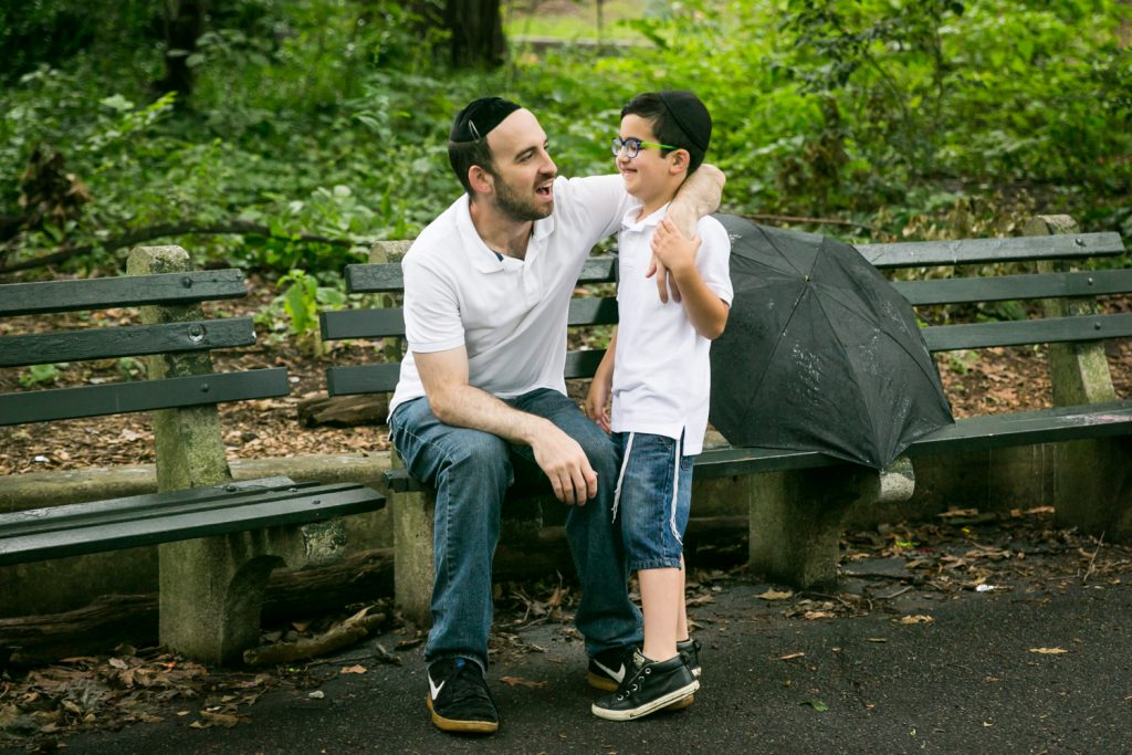 Father sitting on bench in Prospect Park with arm around son