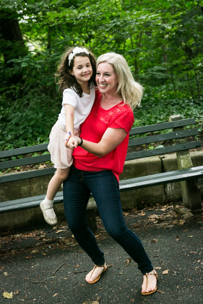 Woman in red holding little girl and dancing in Prospect Park
