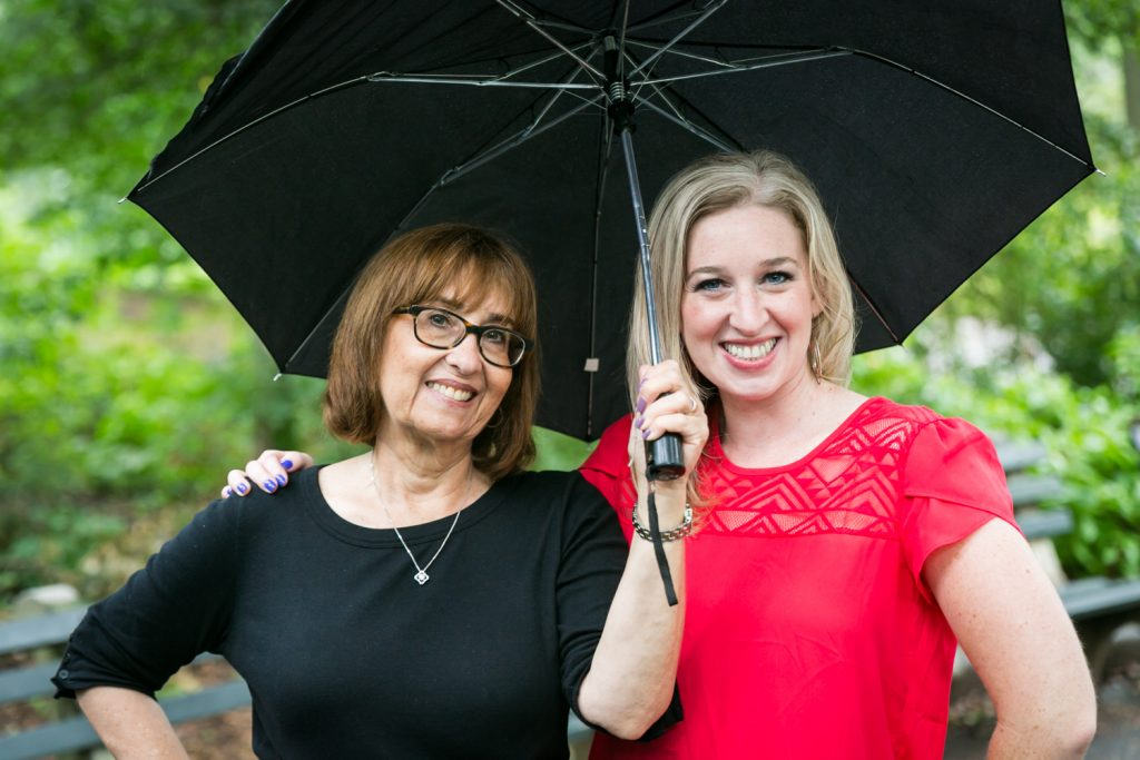 Woman and daughter under black umbrella