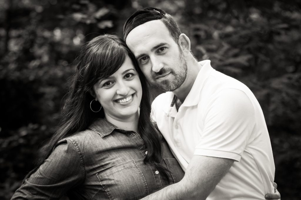 Black and white photo of man hugging his wife in Prospect Park