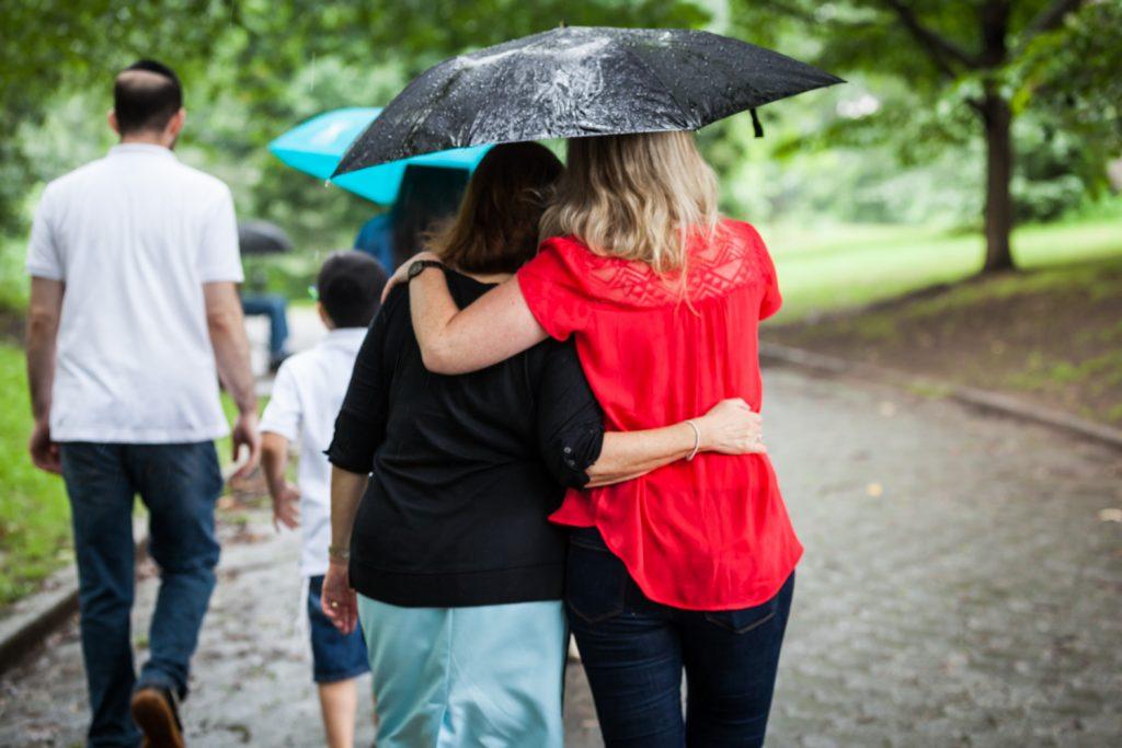 Two women hugging under umbrella and walking away