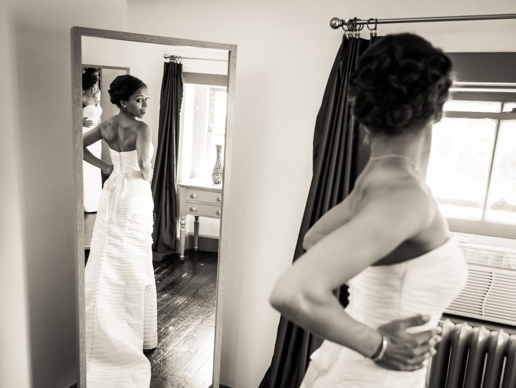 Bride looking at herself in the mirror for an article on when should my wedding photographer arrive