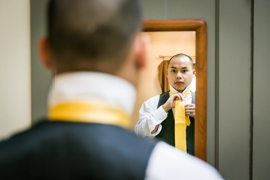 Groom putting on tie in mirror for an article on when should my wedding photographer arrive