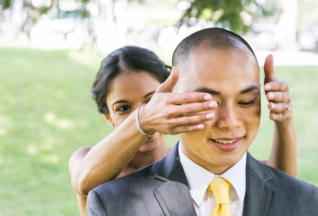 Bride putting hands over groom's eyes for an article on when should my wedding photographer arrive