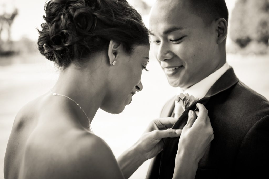 Black and white photo of bride putting boutonniere on groom