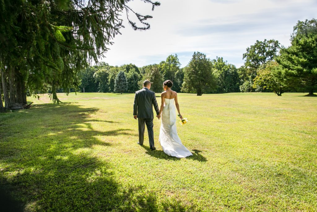 Bride and groom walking hand-in-hand and walking through field