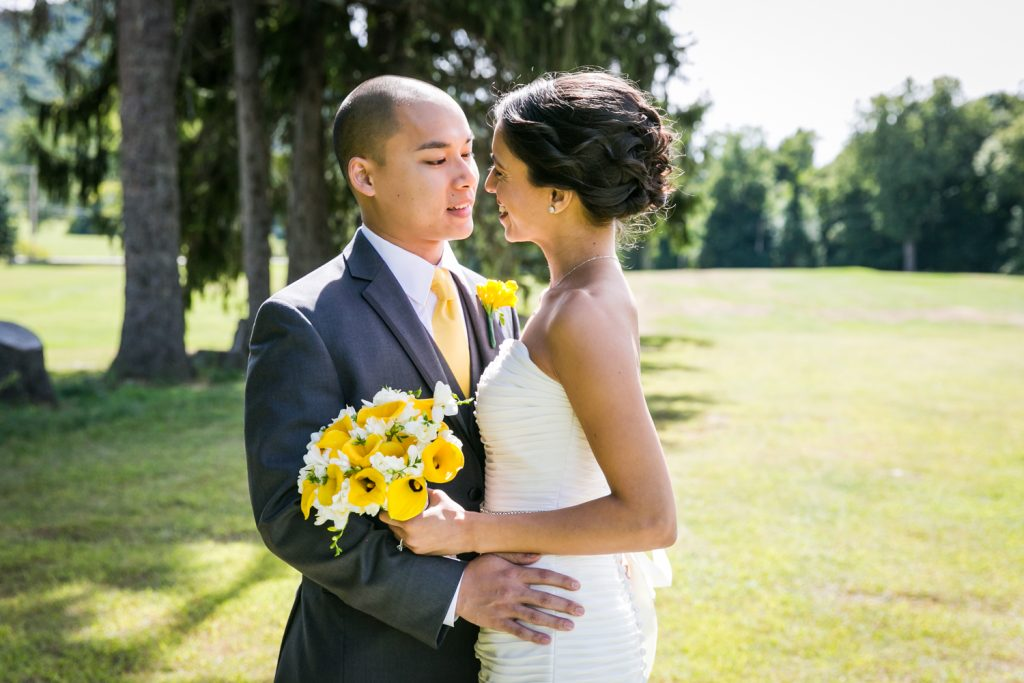 Bride holding bouquet and hugging groom in field