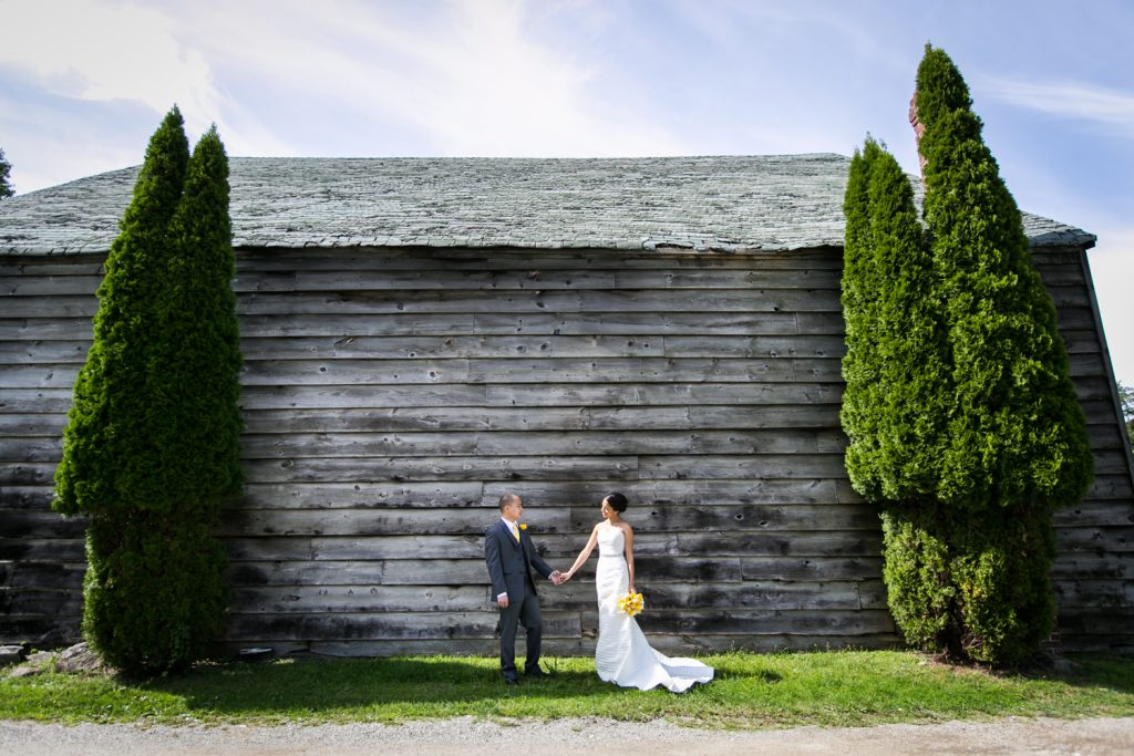 Bride and groom holding hands in front of wooden shed for an article on when should my wedding photographer arrive