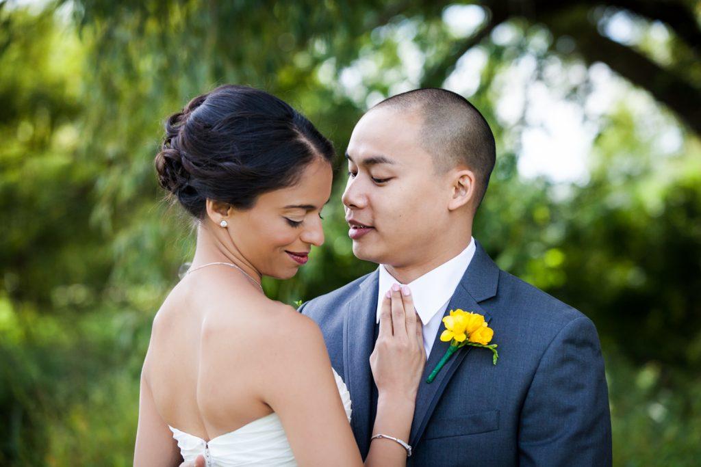 Bride and groom hugging in field