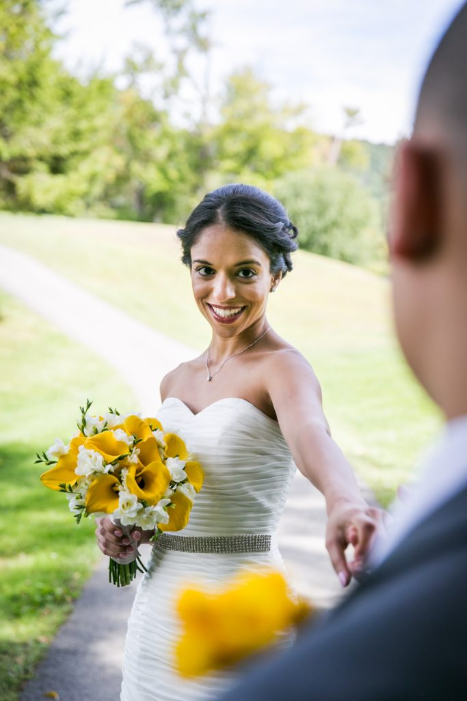 Bride holding bouquet and extending hand to groom