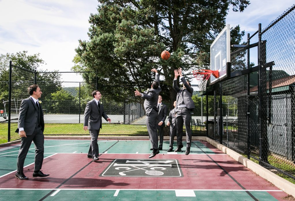 Groom and groomsmen playing basketball in suits