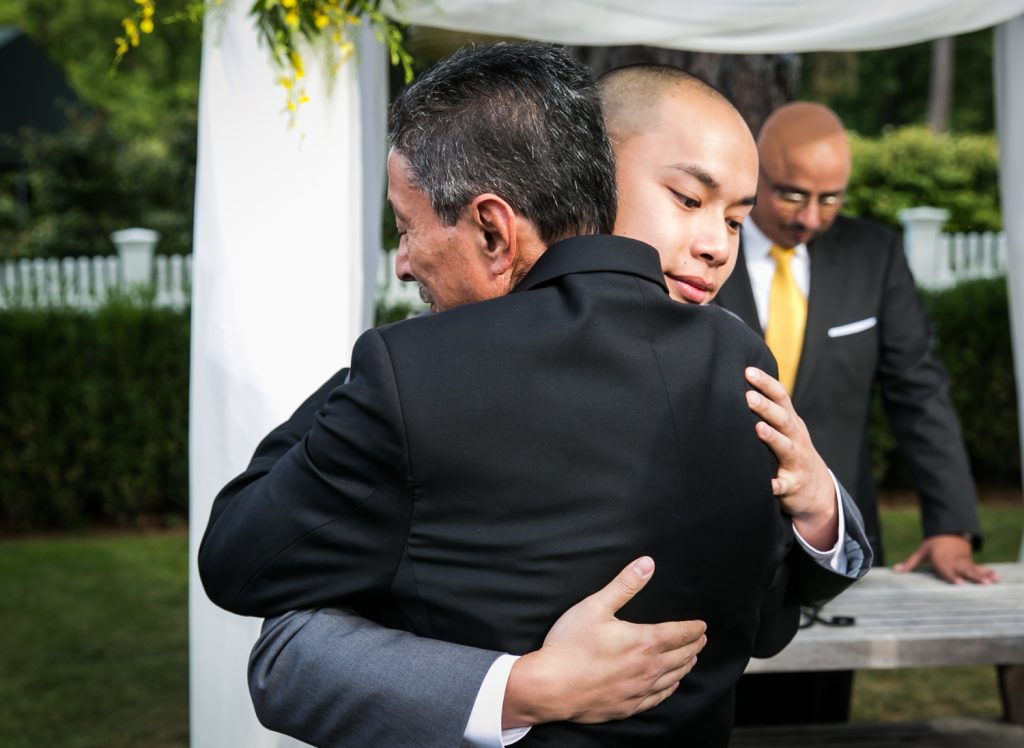 Groom hugging father of the bride at Highlands Country Club wedding ceremony