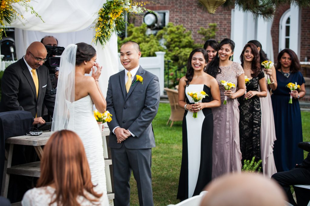 Bride wiping away tear in front of bridal party at Highlands Country Club wedding ceremony